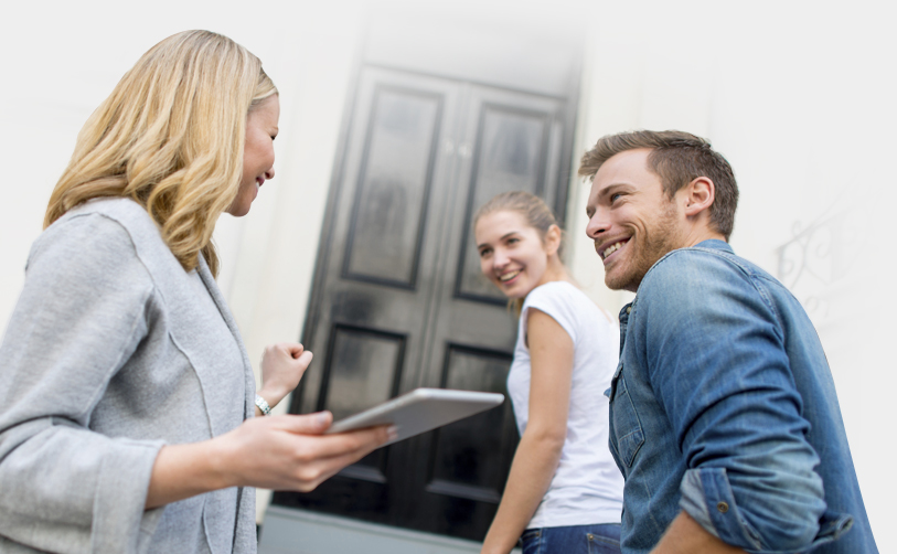 An estate agent showing a couple to a front door of a house